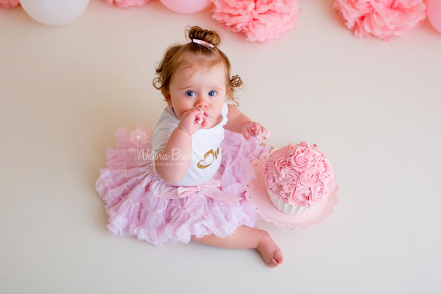 Baby sat on the floor in pink tutu and number one on her top, eating a pink and white cake