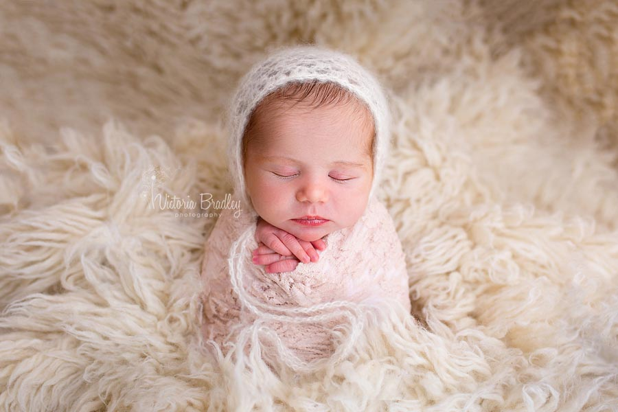 newborn baby girl in the potato sack pose on a cream flokati rug wearing a white mohair bonnet with a blush lace wrap