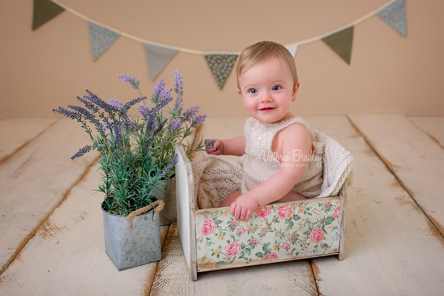 baby girl in vintage garden set, sat in a vintage floral crib with sage bunting and lavender tubs, on cream wooden floorboards