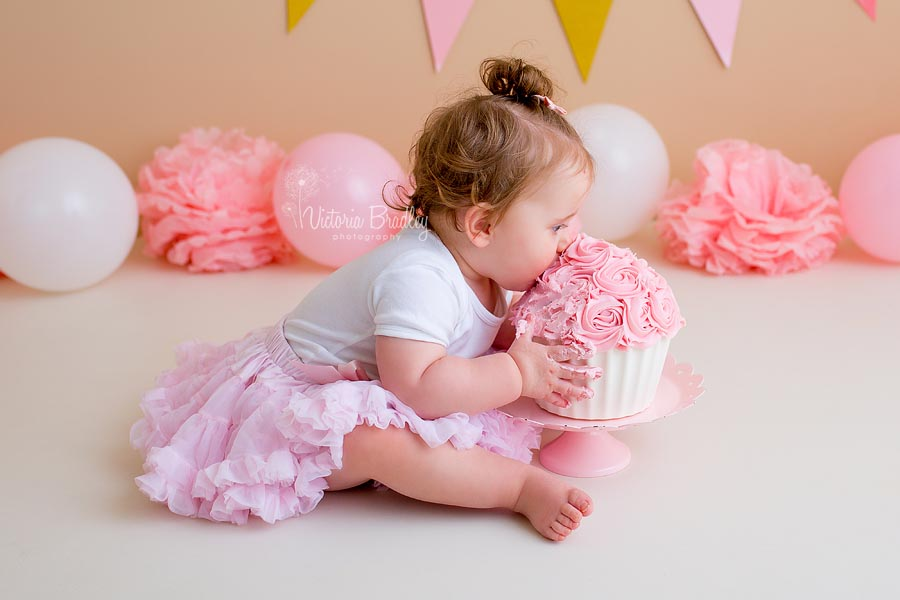 Baby girl eating a pink and white cake, wearing a pink tutu