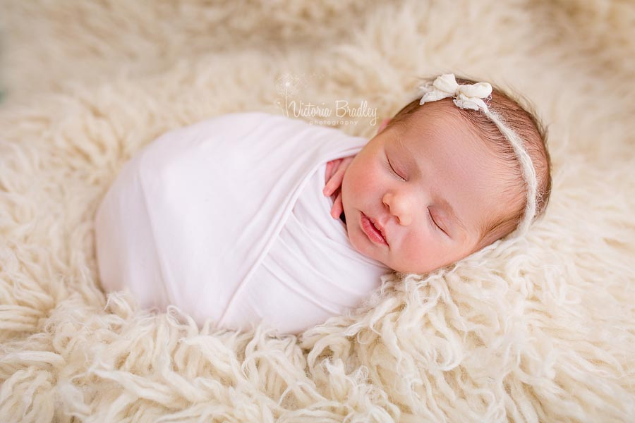 wrapped baby on cream flokati rug with a bow tie back and pale pink wrap