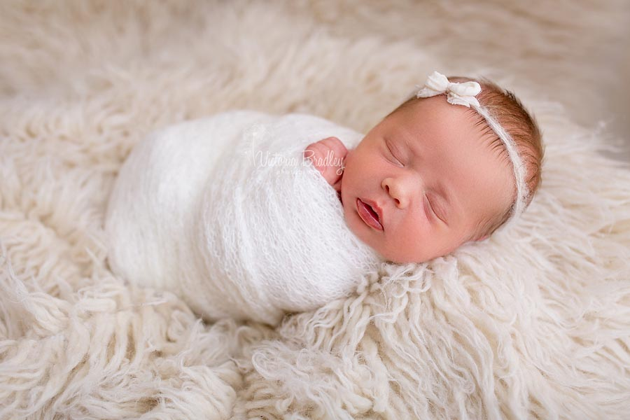 Newborn wrapped baby with bow, cream colours