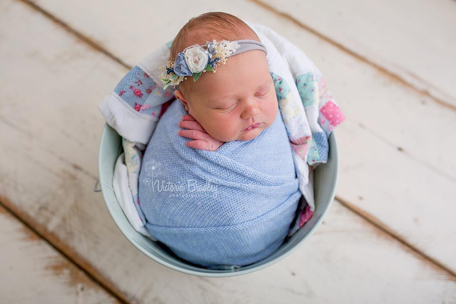 newborn wrapped baby girl in blue, vintage quilt