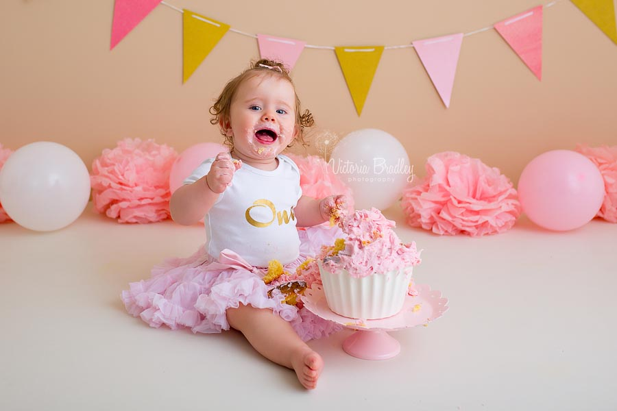 happy baby girl with birthday a pink and white cake for a cake smash