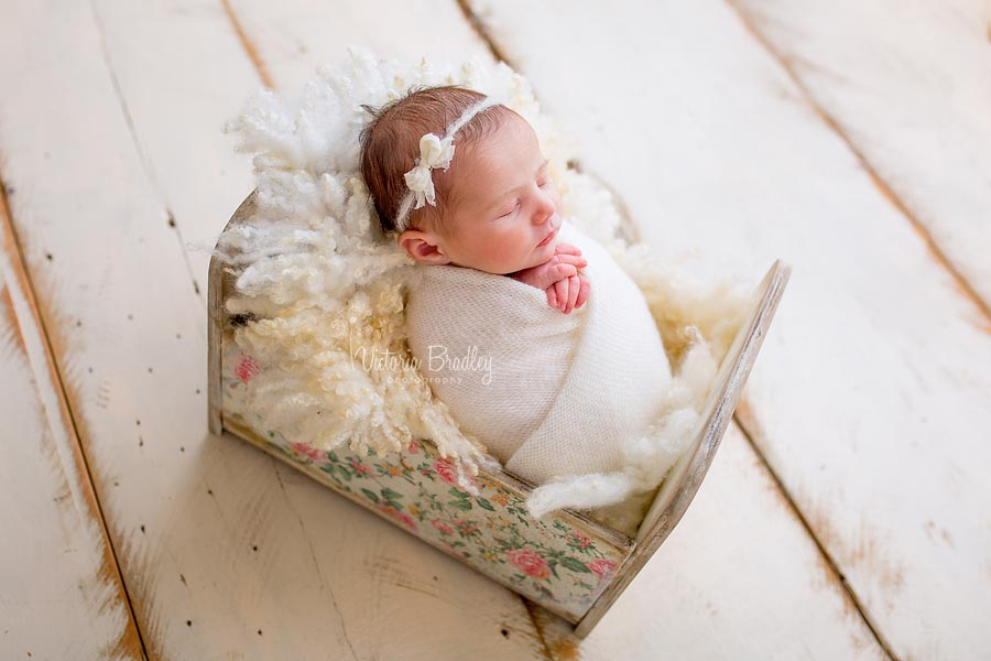 baby in a floral newborn photography crib prop, wrapped in a cream wrap with a bow detail tie back on a cram wood floor