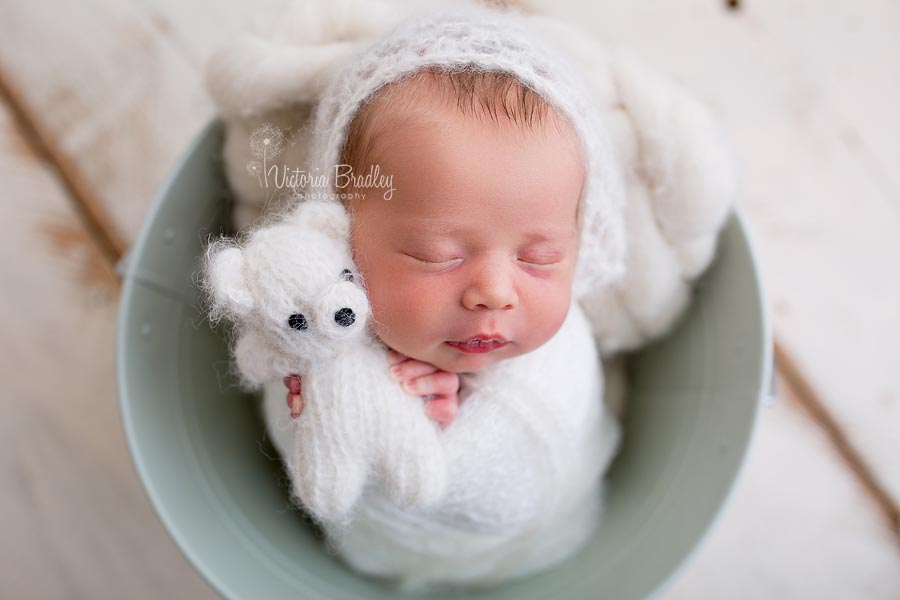 newborn wrapped baby holding little teddy, cream colours