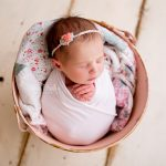 newborn baby in a vintage pink pail swaddled in a pink wrap placed on a wooden painted floor
