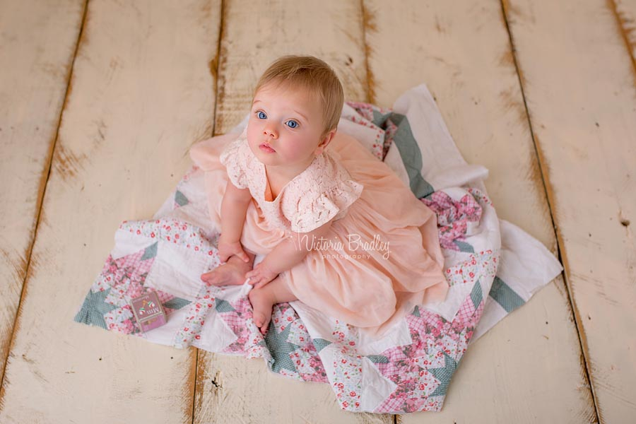 7 month baby girl sat on a pink and sage vintage quilt layer with a peach coloured dress on cream wooden floor boards