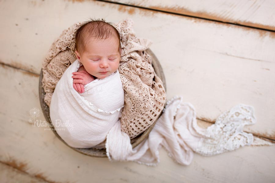 a wrapped baby with vintage lace basket stuffer in a metal bowl on cream wooden floor boards