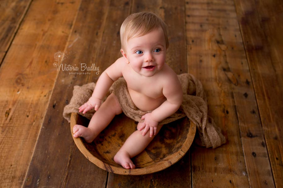 sitter baby girl sat in a wooden bowl on dark wood floor boards