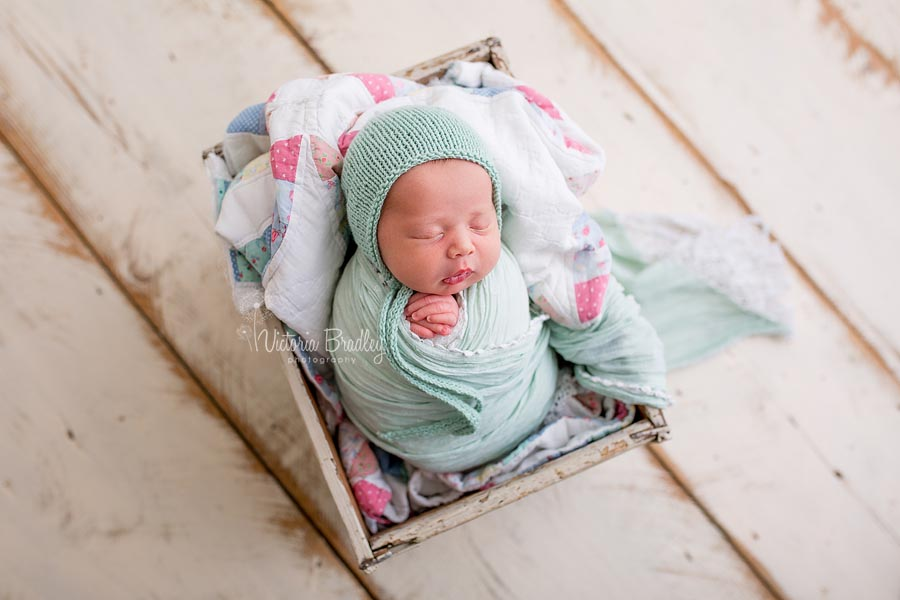 wrapped newborn image with vintage quilt, mint wrap & bonnet