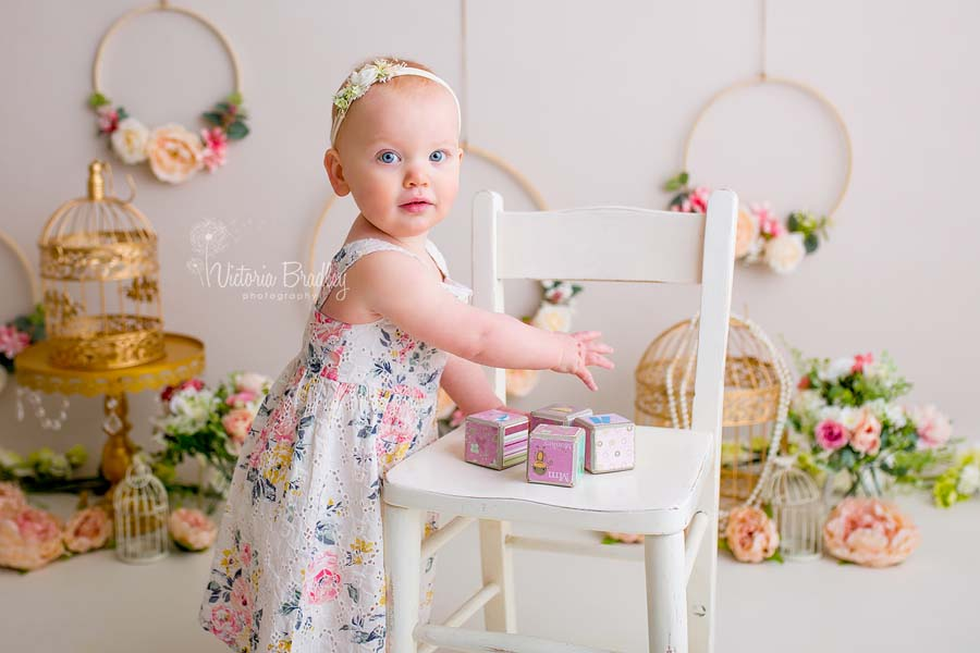 boho floral cake smash with 1 year old baby girl, with flowers, gold bird cages and floral hoops, stood by a white chair