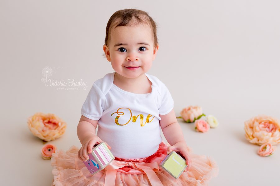 baby girl with peach tutu and peach flowers with a white and gold one top