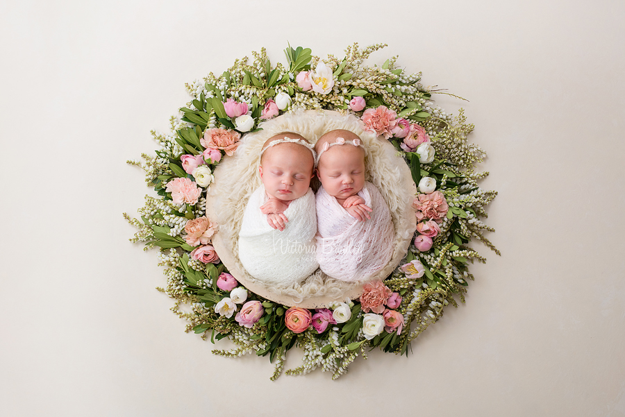 twin newborn babies in floral basket with cream and pink wraps on cream fluffy basket stuffer