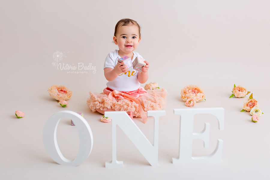 baby girl playing with blocks wearing a peach tutu and white top, with white wooden one letters