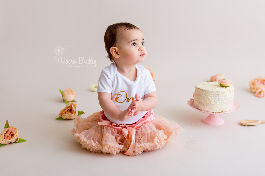 1 year old baby girl birthday cake smash with peach tutu and flowers