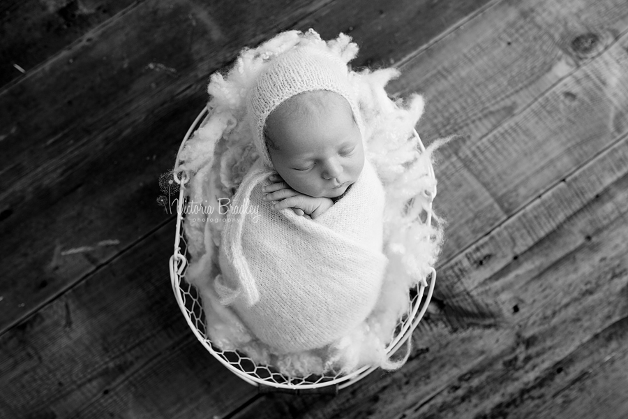 black and white image of a swaddled newborn boy in cream wrap & bonnet on a cream felted curls stuffer in a basket on dark wooden floor boards