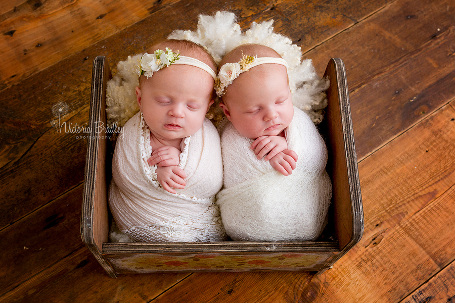 twin newborn girls in wooden crib with cream lace wrap and pretty tie backs