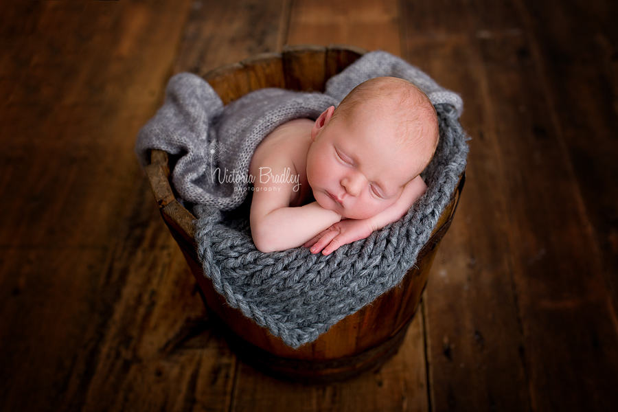 Newborn baby boy in a vintage wooden bucket with a grey knitted layer & grey wrap
