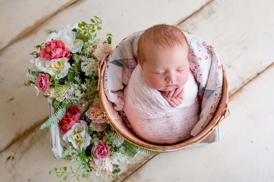 newborn baby girl in vintage pink bucket with a vintage quilt piece, with flowers