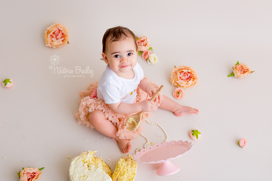 baby playing with wooden spoon and pearls, with a peach tutu and white top with a sponge cake and pink cake stand
