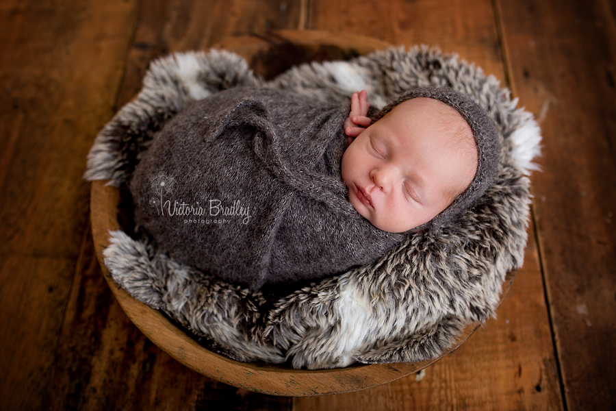 wrapped newborn baby boy on faux fur with dark grey knitted wrap and bonnet in a wooden bowl and a wooden floor