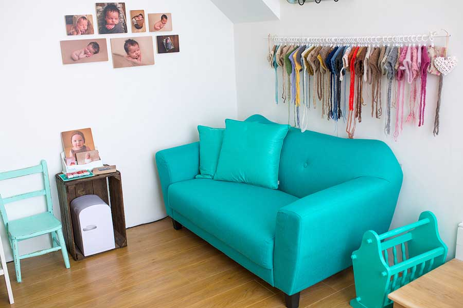 an aqua coloured couch on a wood floor in a white walled studio with photo blocks mounted on the wall