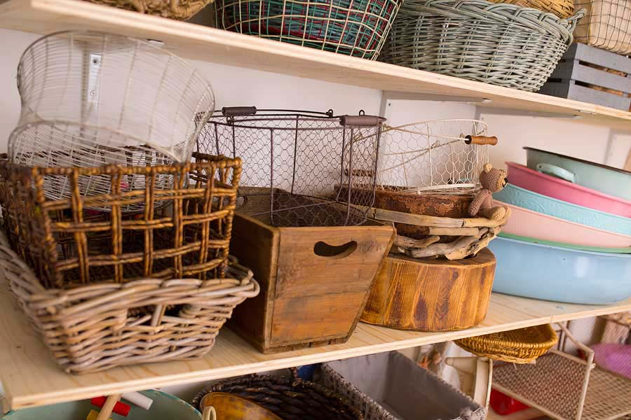 a shelf stacked with various vintage style metal baskets and wooden crates
