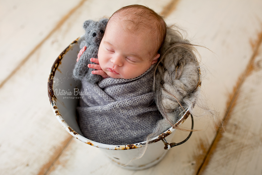 newborn baby boy in grey knitted wrap in a white vintage bucket holding a little knitted grey bear