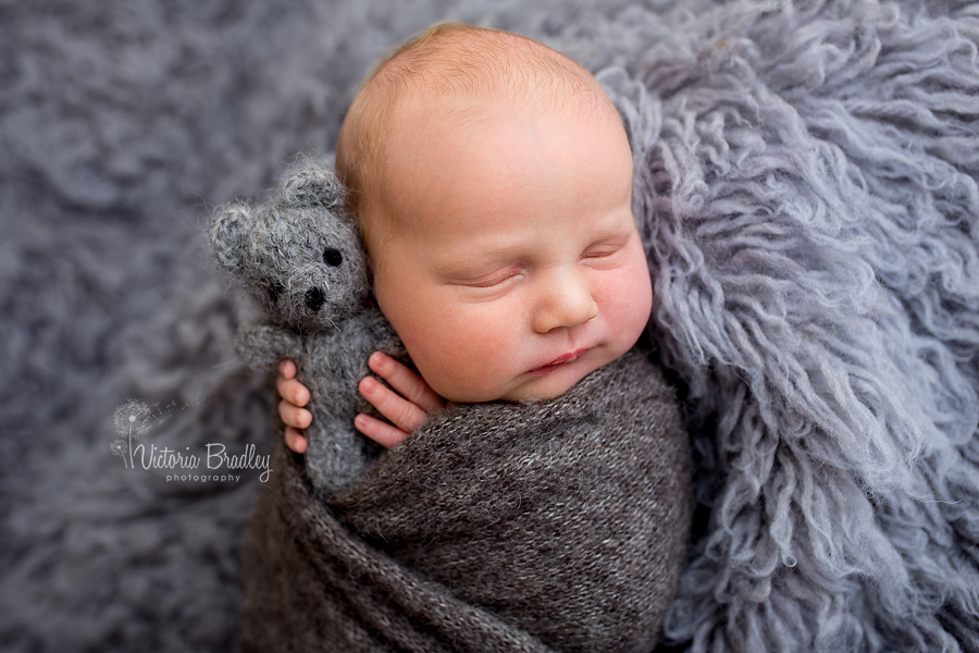 baby wrapped in grey with little grey teddy bear