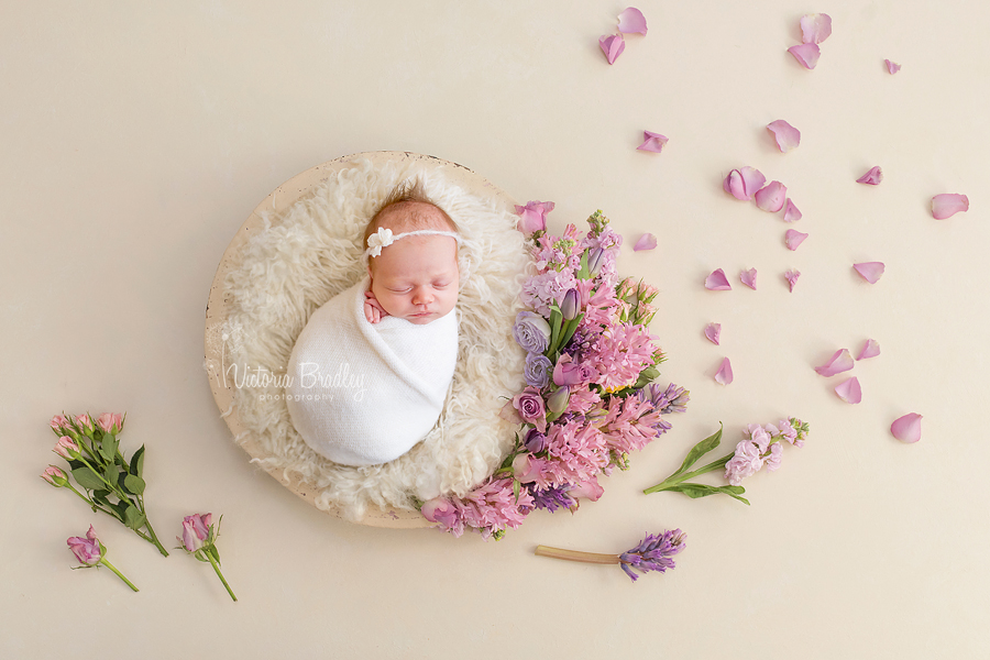 pretty floral bowl with newborn baby girl wrapped in a cream wrap