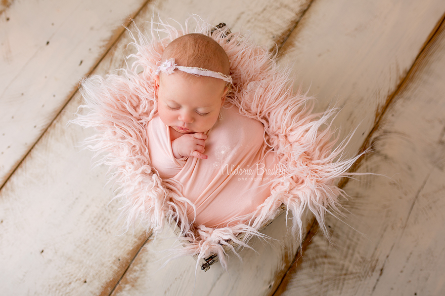 older newborn in peach wrap with peach fur stuffer in cream crate on cream wood floor