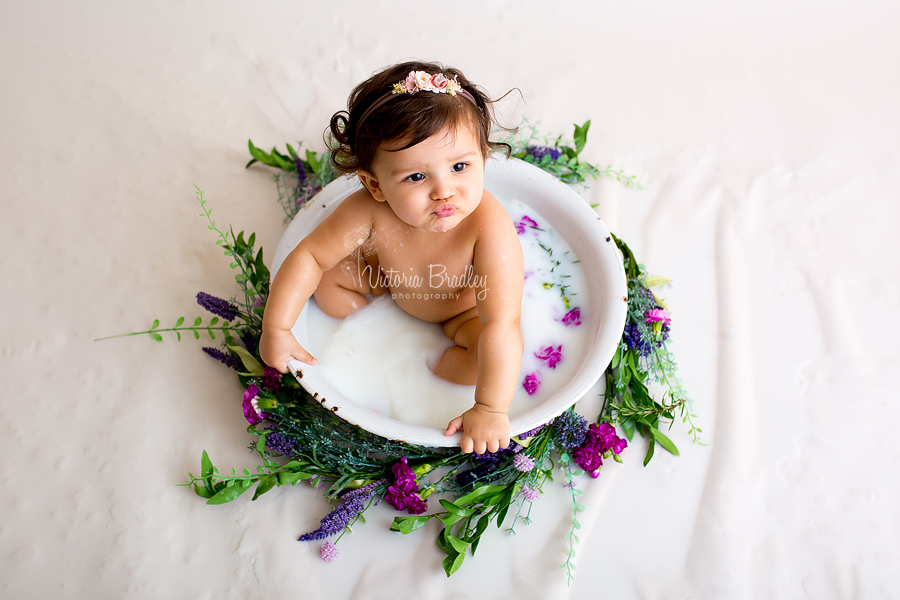 baby in milk bath with purple and green flowers