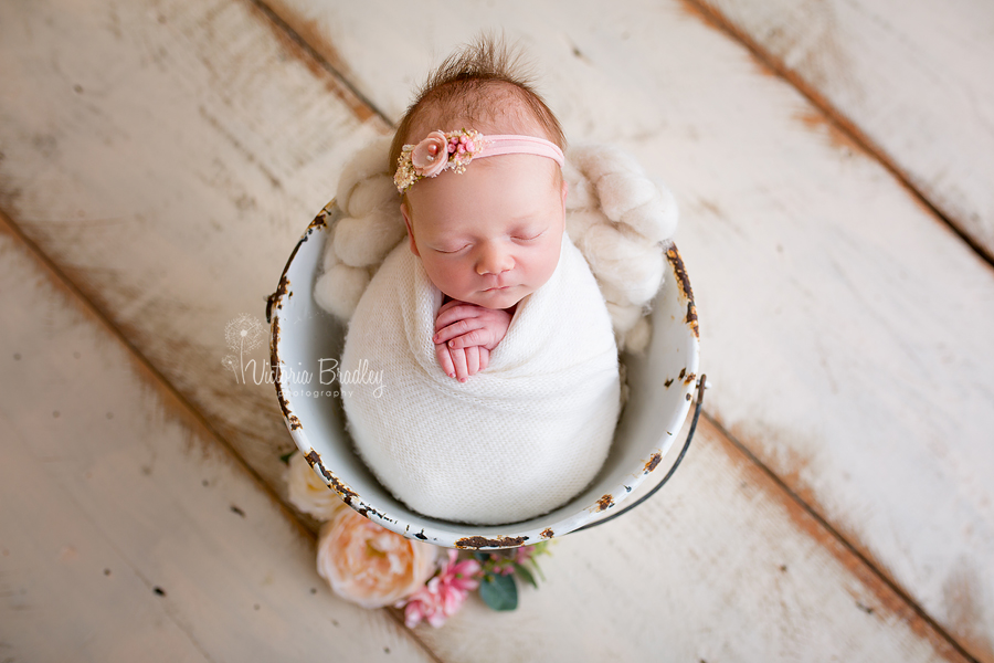 newborn wrapped in a cream knitted wrap in a white vintage pale with flowers on cream wooden floor boards