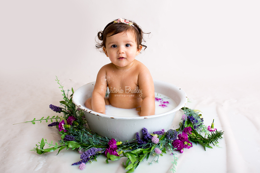 baby girl in white enamel bath tub during milk bath session