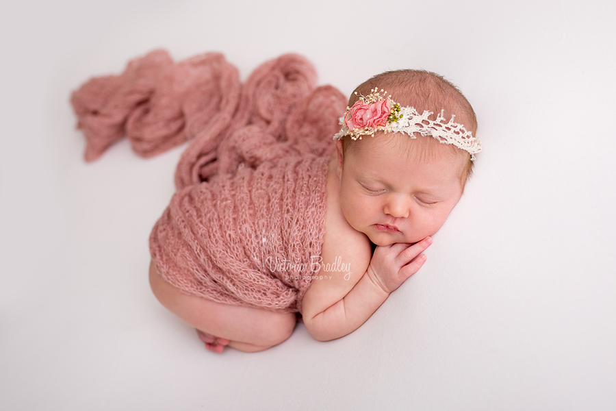 newborn baby lay on her tummy with a pink rose tieback, dusky pink wrap on a cream fabric backdrop