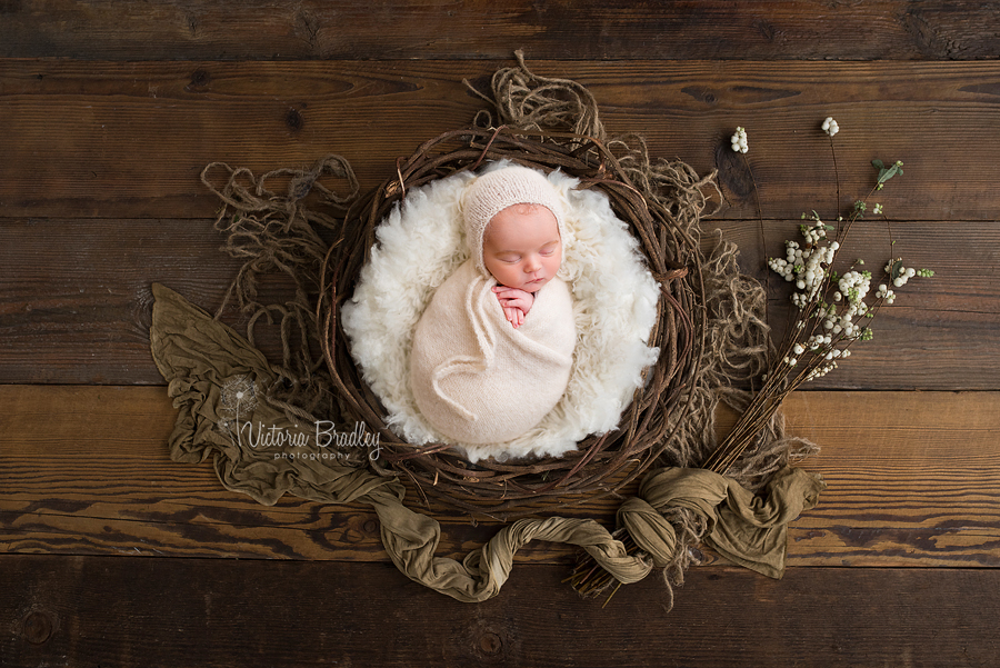 wrapped newborn in cream knitted wrap in a rustic basket