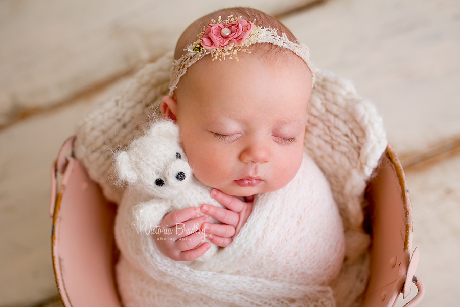 sleepy older newborn holding small cream teddy bear in pink vintage metal bucket