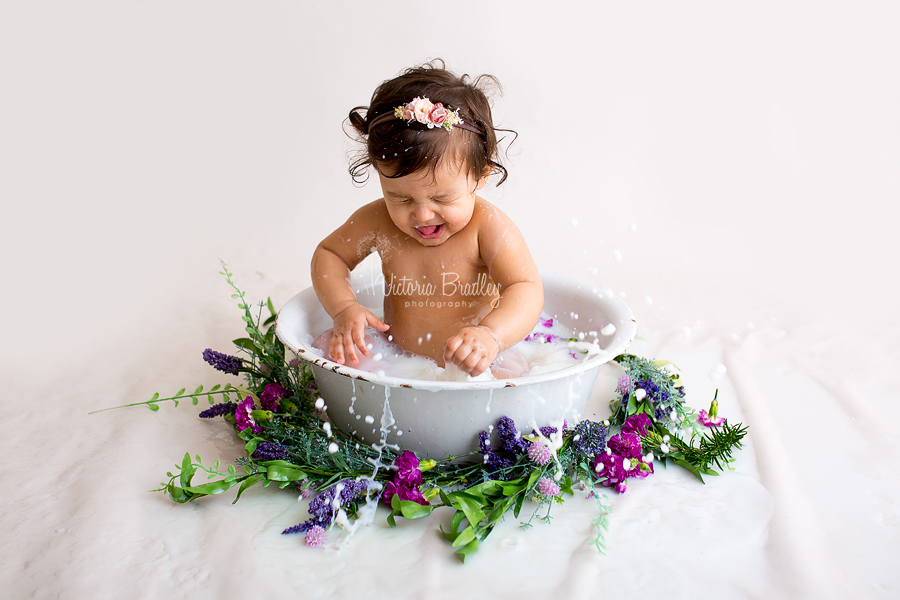 baby girl splashing during a milk bath photography session, using a white enamel bath tub with purple and green flowers and foliage