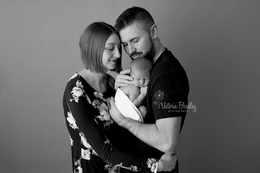 black and white image of a newborn baby with her mummy and daddy on a grey paper backdrop