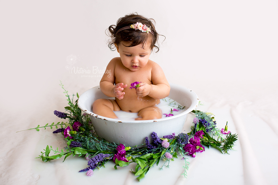baby looking at a purple flower during a milk bath photography session in nottinghamshire