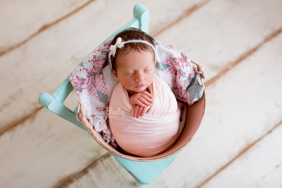 wrapped newborn in pink metal bucket with vintage quilt stuffer on a mint green chair