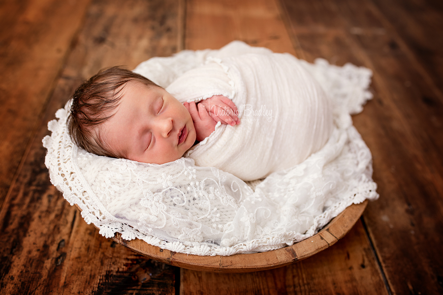 newborn baby girl with cream lace in a wooden bowl on a wooden floor