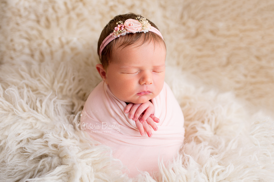 potato sack pose, peach wrap and peach tie back, newborn baby girl on cream flokati rug