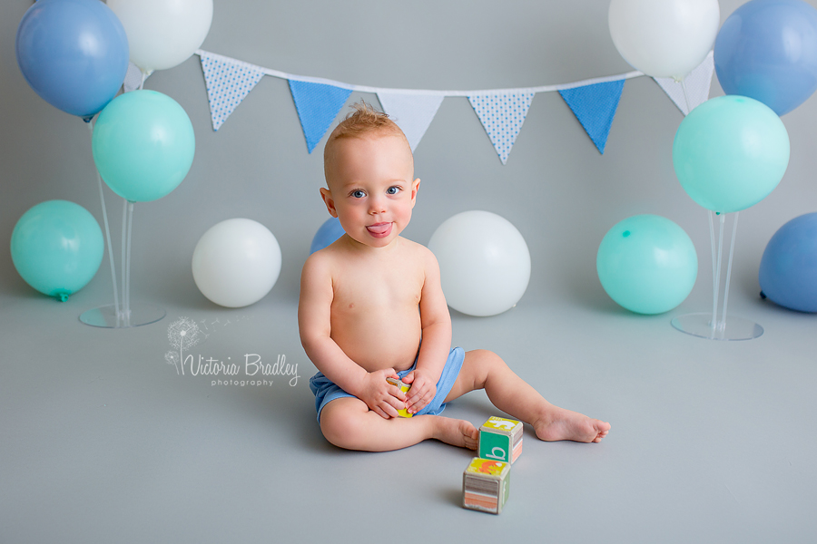 cake smash boy with grey backdrop, blue, mint and white balloons