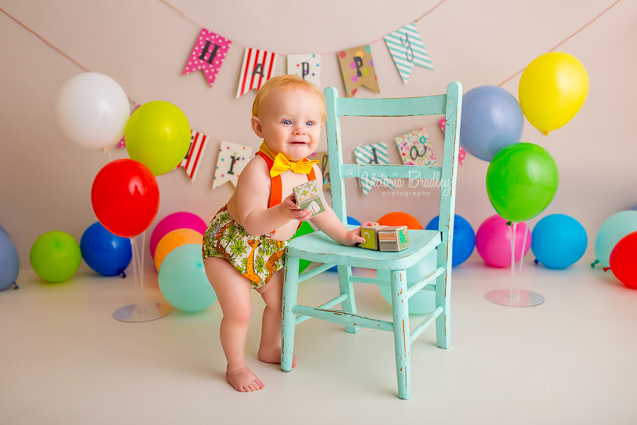 baby boy cake smash, stood next to an aqua chair, holding blocks