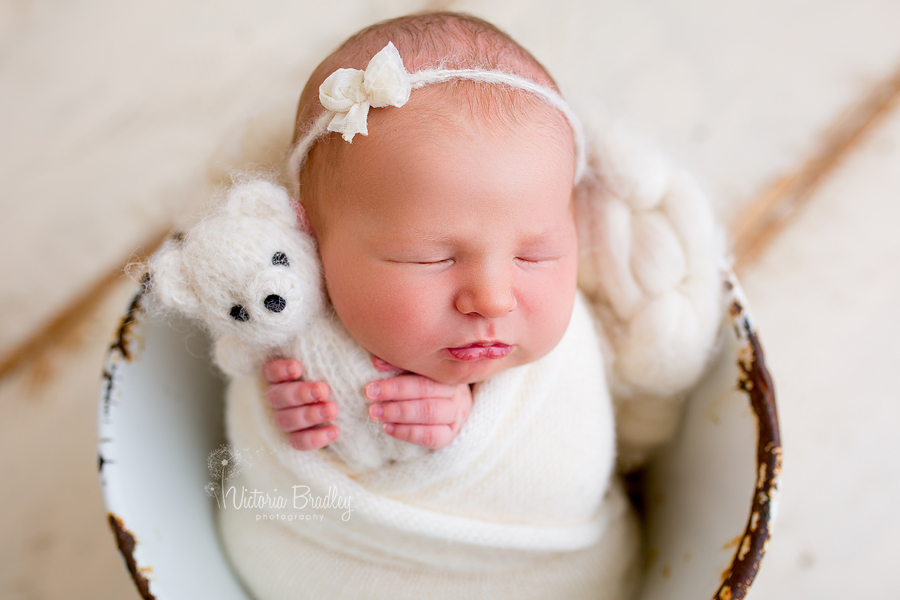 wrapped baby newborn girl with white teddy and white bow hair tie back