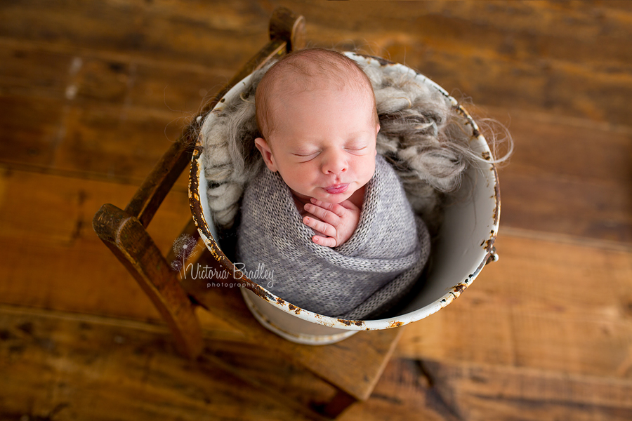 wrapped baby newborn in grey knitted wrap in a white bucket on a wooden chair