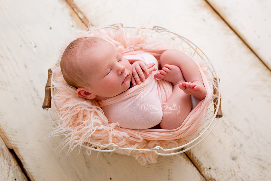 newborn girl in cream egg basket with peach fur stuffer on cream wood floor