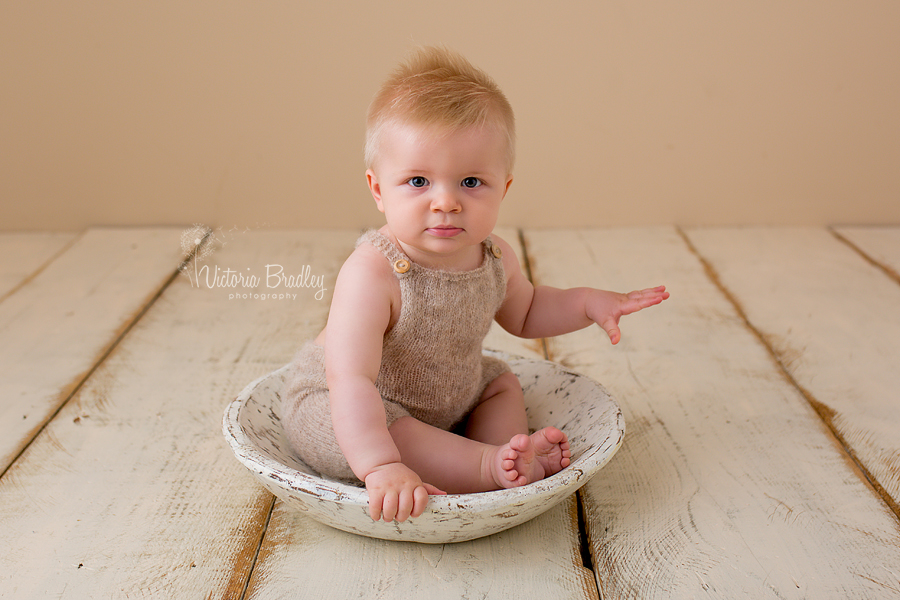 baby boy in knitted rompers in a white wooden bowl on cram wood floor boards